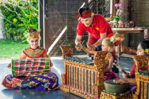 Children wearing Balinese costumes and learning Balinese instruments while on holiday at Citakara Sari Estate