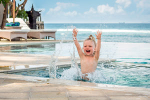 Child enjoying swimming in the ocean-side pool on a family vacation in Bali at Citakara Sari Estate